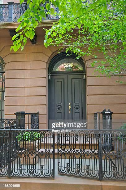 Elaborate fence ironwork, stone wall and door.