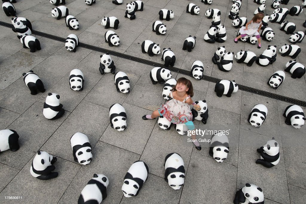 Elaia (C), 6, and her sister Lusitta, 4, play among 1,600 styrofoam panda bear sculptures displayed in front of Hauptbahnhof main railway station by the World Wildlife Fund on August 5, 2013 in Berlin, Germany. The WWF is celebrating its 50th anniversary and is drawing attention to the fact that only 1,600 panda bears remain in the wild. The display will soon travel to 25 other cities in Germny.