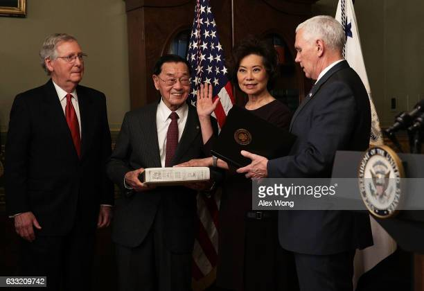 Elaine Chao is sworn in by US Vice President Mike Pence as her father James Chao and her husband Senate Majority Leader Sen Mitch McConnell look on...