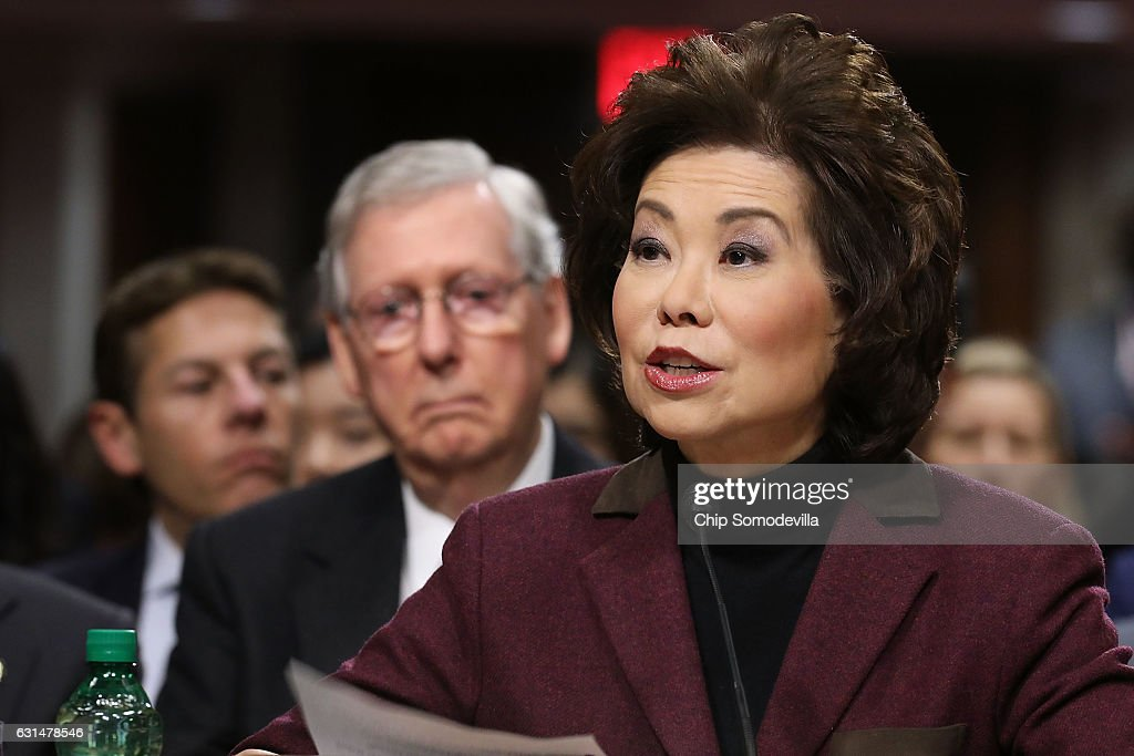 Elaine Chao testifies during her confirmation hearing to be the next U.S. secretary of transportation before the Senate Commerce, Science and Transportation Committee as her husband, Senate Majority Leader Mitch McConnell (R-KY) (2nd L) looks on, in the Dirksen Senate Office Building on Capitol Hill January 11, 2017 in Washington, DC. Chao, who has previously served as secretary of the Labor Department, was nominated by President-elect Donald Trump.