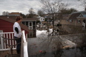 Elaine Hague looks over her flooded back yard on November 1 2012 in the Ocean Breeze area of the Staten Island borough of New York City Most homes in...
