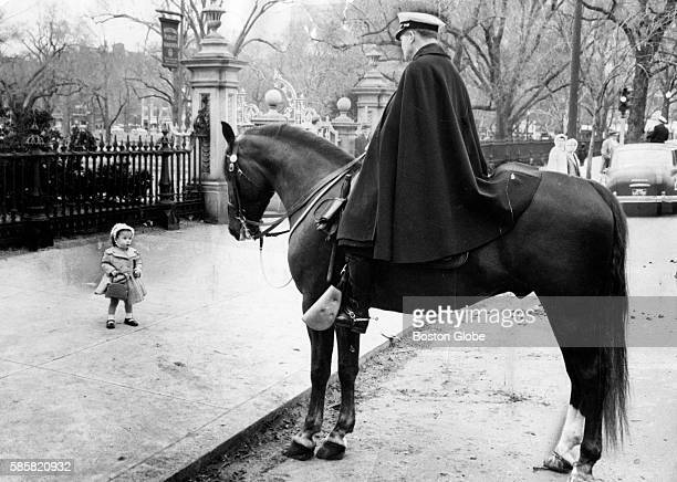 Elaine Martin stops to look at Officer Benjamin Donahue aboard his horse Justin's Son near the Public Garden in Boston on April 6 1958