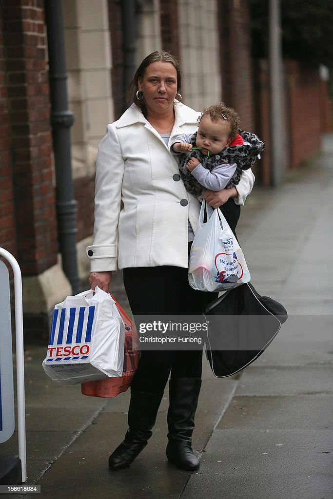 Elaine Oliver holds her daughter Safiyah Lesley, aged 14 months, after collecting essential Christmas food on December 21, 2012 in Liverpool, England. Elaine, who is a mother of five, had her home burgled this week and had all of the children's Christmas presents and family housekeeping money stolen and had to turn to the Foodbank to help them through Christmas. With Christmas only days away, volunteers at the Central Liverpool Foodbank at the Frontline Trust, have seen one of their busiest days of the year as they give out free food for the needy. The centre has been giving out festive treats as well as its normal food donation - feeding over 1000 individuals in its first year, including over 300 children..