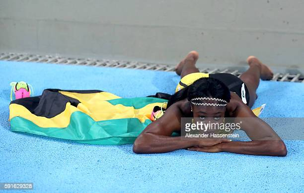 Elaine Thompson of Jamaica celebrates with the flag of Jamaica after winning the gold medal in the Women's 200m Final on Day 12 of the Rio 2016...