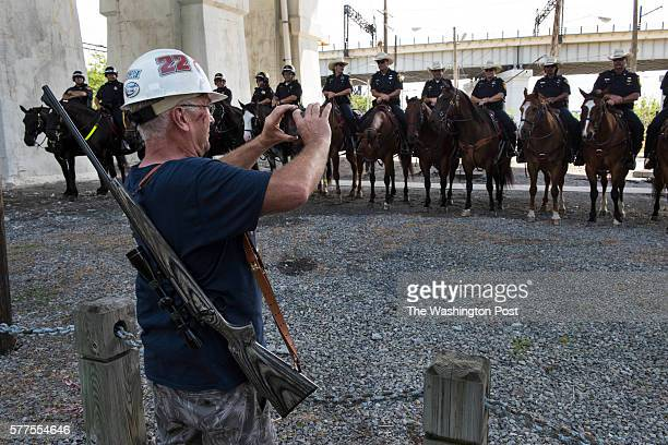 Elam Stoltzfus of Lancaster Pa carrying his hunting rifle photographs a phalanx of mounted police officers near a proTrump rally in Cleveland on July...
