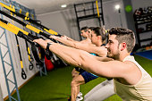 Group of people trainung in elastic rope at modern gym