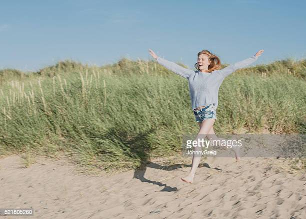 Elated young woman running onto sandy beach