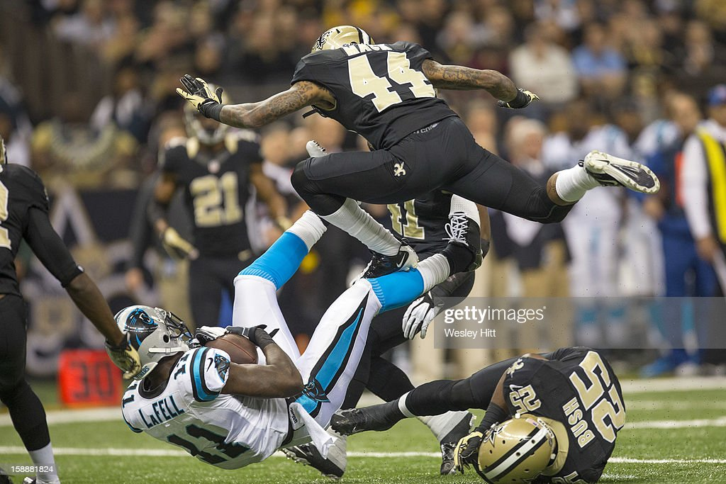 Elbert Mack #44 of the New Orleans Saints jumps over the tackle of Brandon LaFell #11 of the Carolina Panthers at Mercedes-Benz Superdome on December 30, 2012 in New Orleans, Louisiana. The Panthers defeated the Saints 44-38.
