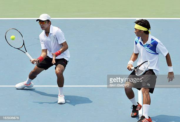 Elbert Sie and Christopher Benjamin Rungkat of Indonesia return a shot against Ruben Gonzales and Treat Conrad Huey of the Philippines during the...