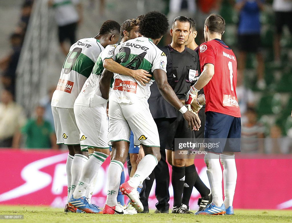 Elche's players argue with referee Muniz Fernandez during the Spanish league football match Elche vs Real Madrid at the Manuel Martines Valero Stadium in Elche on September 25, 2013.