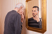 Elder man looking at an younger himself in the mirror