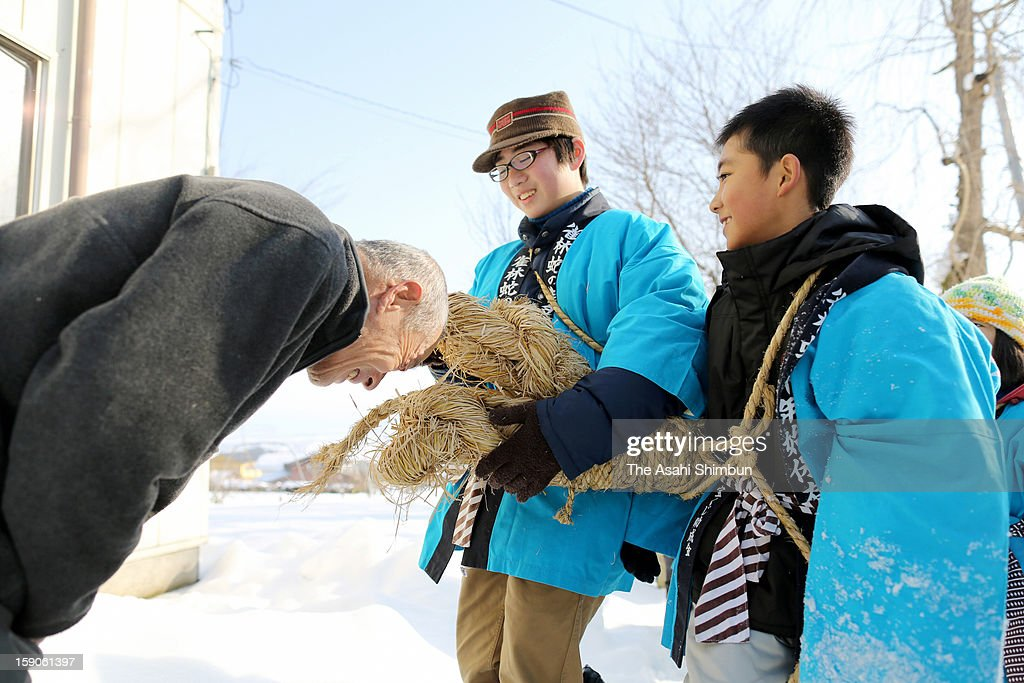 A elder man makes his head bitten by a 7-meter-long, 30-kilogram straw snake carried by school pupils in hope of good health during the Hebi-no-Gonenshi, or Snake's New Year on January 7, 2013 in Aizumisato, Fukushima, Japan. The event, has more than 120 years tradition, started in Meiji Period when local people suffered from water shortage prayed to a straw snake.