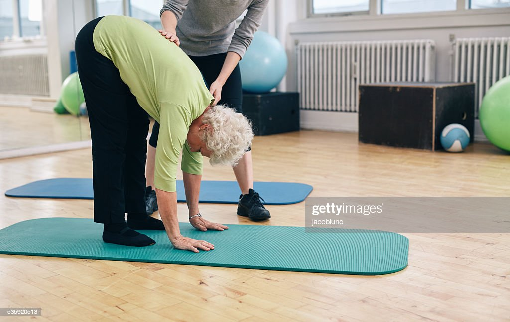 Elder woman exercising with help from trainer : Stock Photo