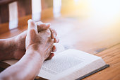 Elder woman hands folded in prayer on a Holy Bible  for faith concept in vintage color tone