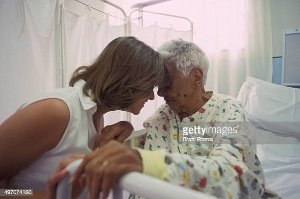 Elderly and disabled patient cared by young doctor in geriatric hospital that takes in chronically paralyzed patients or those totally dependent on...