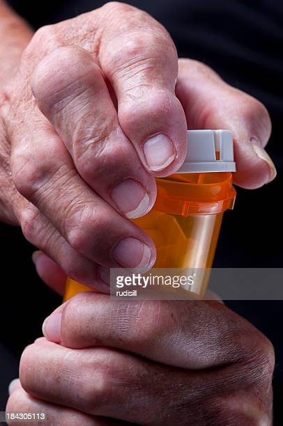 Elderly, arthritic hands opening a pill bottle