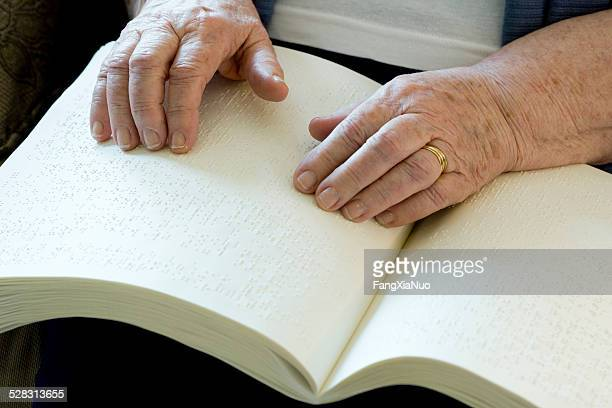 Elderly Blind Woman Reading Book With Her Hands
