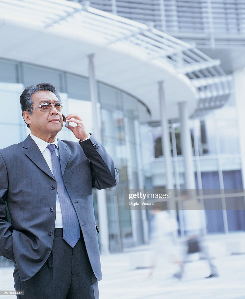 Elderly Businessman Stands Holding Mobile Phone Outside Glass Office Block : Stock Photo
