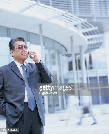 Elderly Businessman Stands Holding Mobile Phone Outside Glass Office Block : Foto de stock