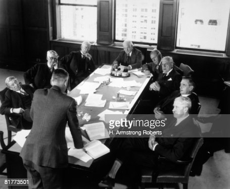 Elderly Businessmen At Conference Table With 1 Man Standing & Talking  : Stock Photo