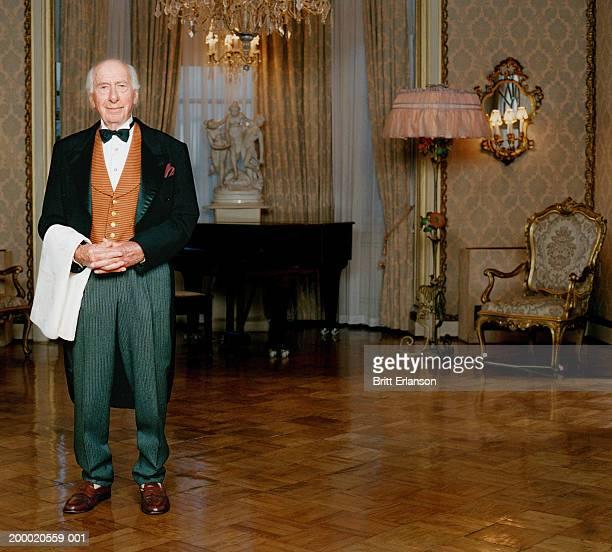 Elderly butler standing in room, portrait