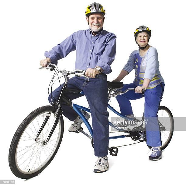 Elderly caucasian couple rest on a tandem bike.