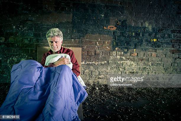 Elderly caucasian homeless man with sleeping bag in subway tunnel