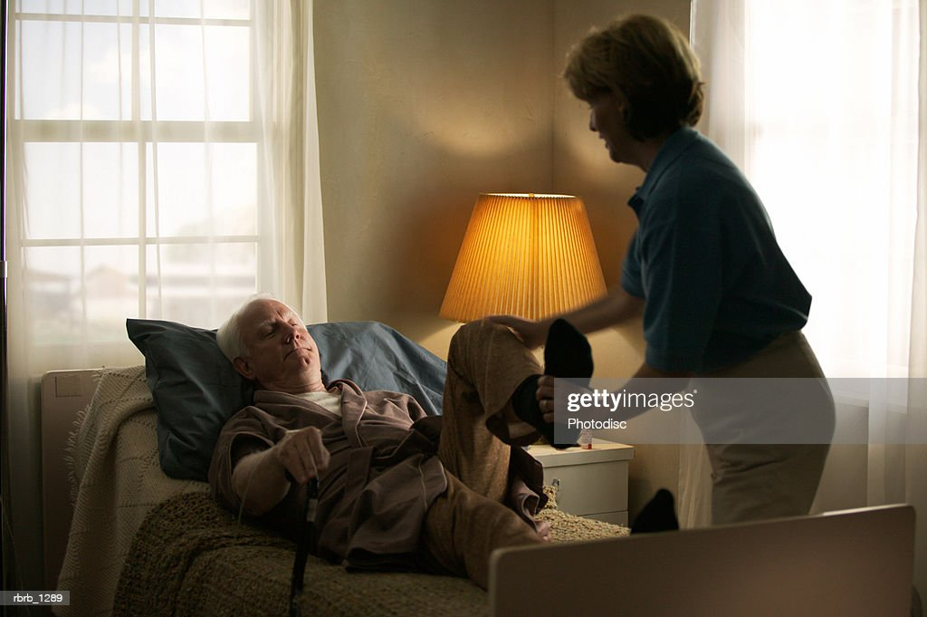 elderly caucasian man in a brown robe lays in bed and gets some physical therapy from a home nurse : Stock Photo