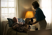 elderly caucasian man in a brown robe lays in bed and gets some physical therapy from a home nurse
