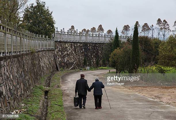 Elderly Chinese couple Qiu Farong left and wife Wei Chaidi walk downt he road after prayers and lunch at the Ji Xiang Temple and nursing home on...