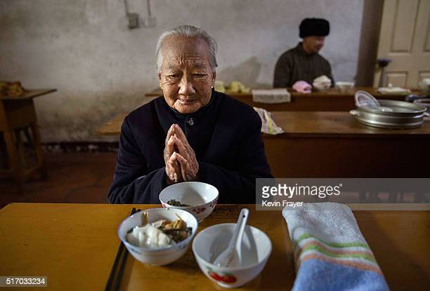 Elderly Chinese resident Chen Minying prays before lunch in the dining hall of the Ji Xiang Temple and nursing home on March 17 2016 in Sha County...
