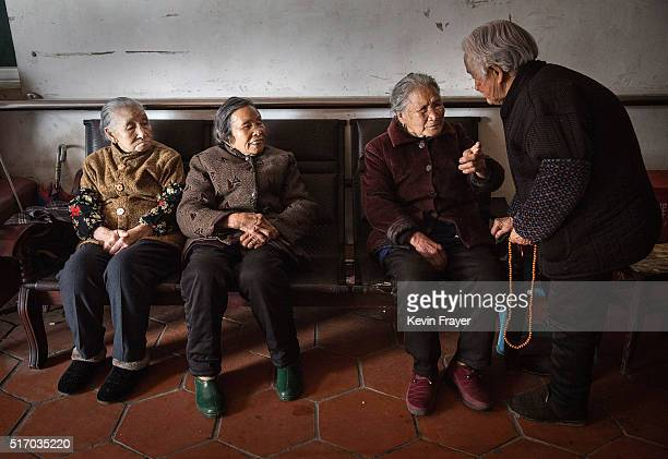 Elderly Chinese residents chat as they wait before a meal at the Ji Xiang Temple and nursing home on March 18 2016 in Sha County Fujian province...