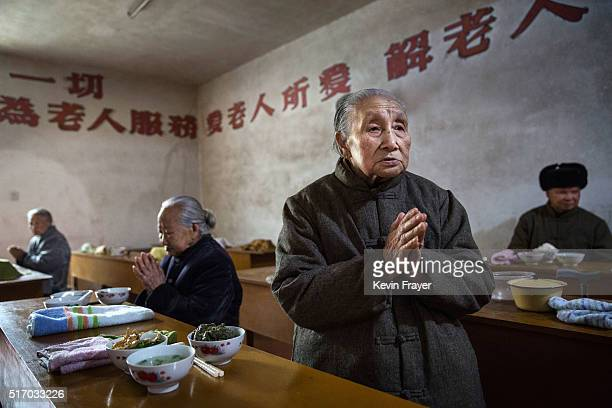 Elderly Chinese residents pray before lunch in the dining hall of the Ji Xiang Temple and nursing home on March 17 2016 in Sha County Fujian province...