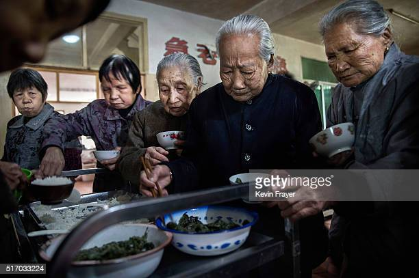 Elderly Chinese residents serve themselves lunch in the dining hall of the Ji Xiang Temple and nursing home on March 17 2016 in Sha County Fujian...