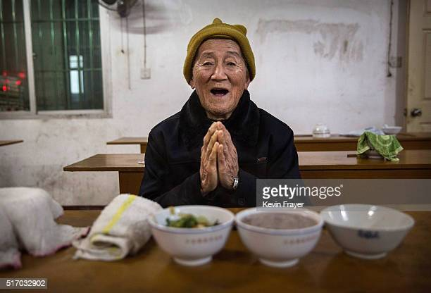 Elderly Chinese villager Hong Meizi prays before a meal at the Ji Xiang Temple and nursing home on March 17 2016 in Sha County Fujian province China...