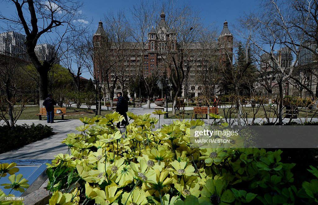 Elderly Chinese walk in a city park beside recently renovated historic building in the foreign concession area of Tianjin on April 6, 2013. The city has almost completed a program of restoring its foreign buildings to their former condition. AFP PHOTO/Mark RALSTON