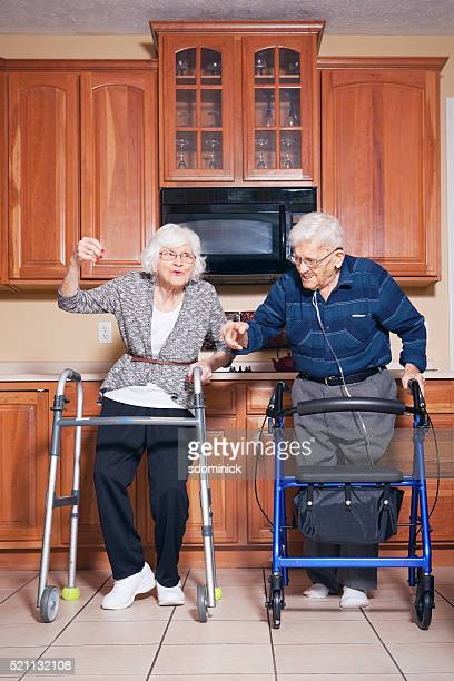 Elderly Couple Dancing In Kitchen Together