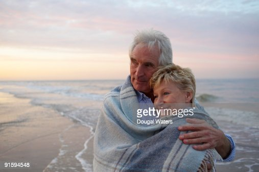 Elderly couple embracing at beach. : Stock Photo