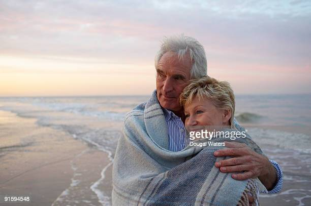 Elderly couple embracing at beach.