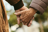 Close up of elderly couple holding hands and walking outdoors. Rear view of man and woman holding hands of each other while walking outdoors.