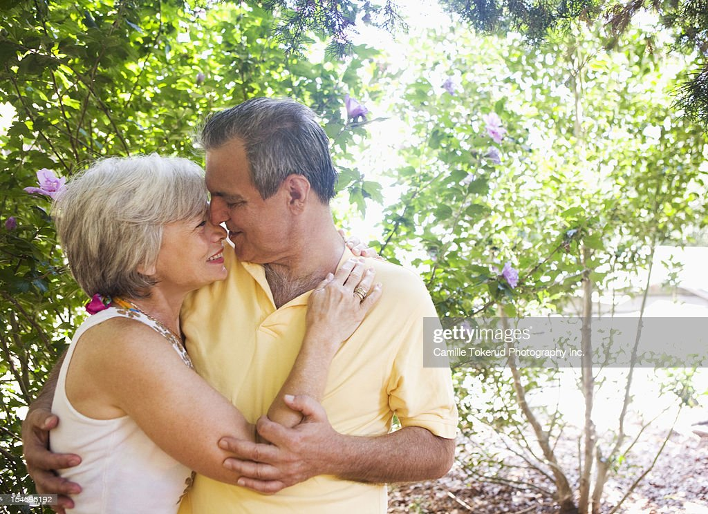 Elderly couple hugging outdoors : Stock Photo