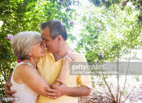 Elderly couple hugging outdoors : Stock Photo