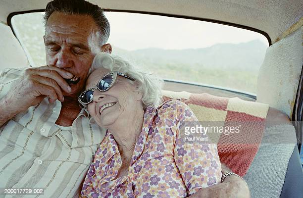 Elderly couple in car, man playing harmonica, close-up