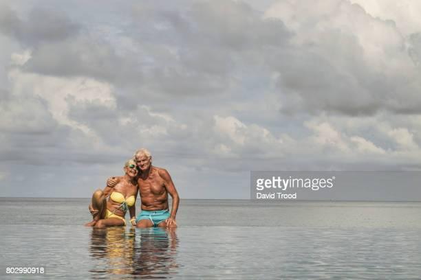 Elderly couple in infinity pool