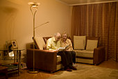 Elderly couple looking at photo album in living room