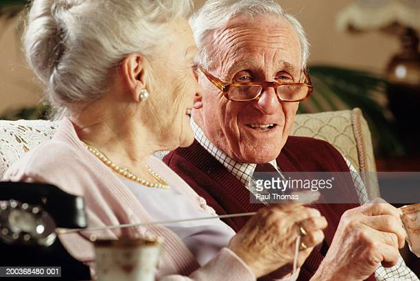 Elderly couple on couch in living room, close-up