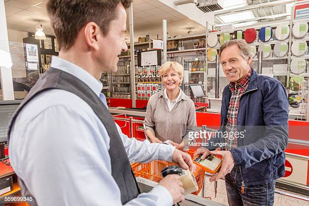 Elderly couple paying at the cash box