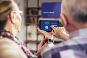 Elderly couple sitting comfortably on a sofa with their backs holding remote home control system on a digital tablet