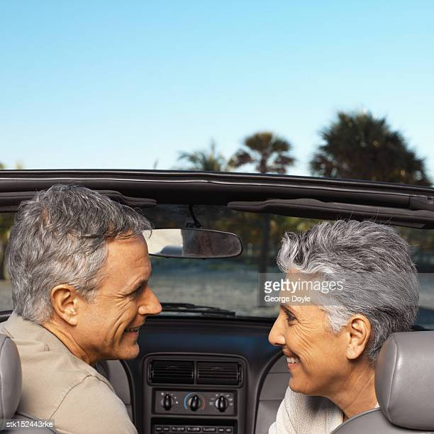 Elderly couple sitting in a convertible car looking at each other