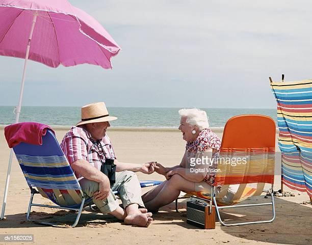 Elderly Couple Sitting on Deck Chairs and Holding Hands on a Beach